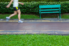 Legs view of Jogging against a green bench Stock Photo