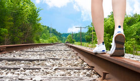 Legs walking along train tracks Royalty Free Stock Image