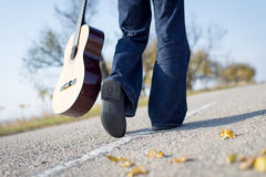 Legs walking away with guitar aside on empty Stock Photos