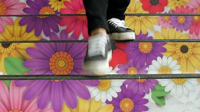 Legs walking up stairs with flower art stock footage