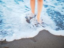 Legs in waves at beach. Close up of legs and feet in waves of ocean along sandy beach in daylight Stock Photography