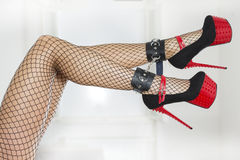Legs wearing fishnet stockings, ankle cuffs and extreme high hee. Legs of a woman in fishnet stockings and extreme red platform shoes with ankle cuffs Stock Photo