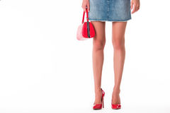Legs wearing heels and purse. Short blue denim skirt. Attractiveness and youth. Emphasize the femininity Royalty Free Stock Images