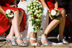 Legs in wedding. Feet of the bride among two bridesmaids sitting on chairs holding white flower bouquet in their lap and wearing beautiful shoes Royalty Free Stock Image