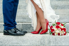 Legs of wedding couple and bouquet. Legs of wedding couple on stone stairs and bouquet Royalty Free Stock Images