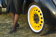 Legs and wheel. A pair of stylish ladies legs in front of a colourful car wheel Stock Photography