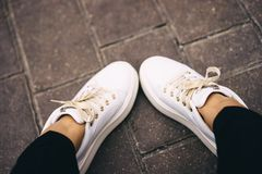 Legs in white sneakers with gold laces. Relaxation. Shopping concept. Fitness concept royalty free stock image