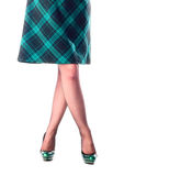 Legs of woman. In green stilettos and black and green cells skirt Stock Photography
