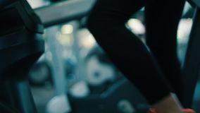 Legs of woman as she works out on Elliptical machine at gym stock video footage