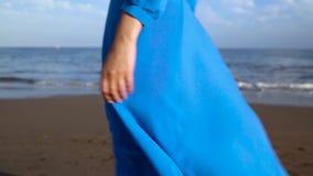 Legs of a woman in beautiful blue dress walking along a black volcanic beach stock video footage