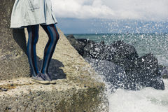 Legs of woman in dress standing on coast Royalty Free Stock Photo