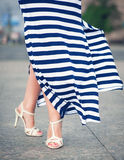 Legs of woman dressed long fluttering striped dress Stock Image