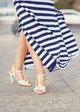 Legs of woman dressed striped dress Stock Photography