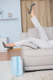 Legs of woman with heels lying on couch Royalty Free Stock Photography