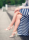 Legs of woman with high heels dressed long striped dress. Outdoor Stock Photo