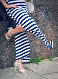 Legs of woman with high heels dressed long striped dress Stock Image