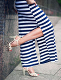 Legs of woman with high heels dressed long striped dress Stock Images