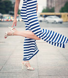 Legs of woman with high heels dressed long striped dress. Outdoor in the city Stock Photography