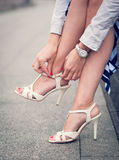 Legs of woman with high heels white sandals Stock Photos