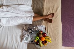 Legs of woman lying on bed with plate of fruits stock photography