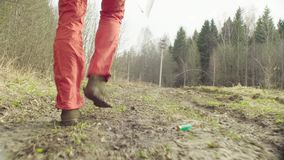 The ecologist going to the place of research. Legs of the woman moving on the dirty road in a spring forest. The scientist ecologist going to the place of stock footage