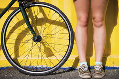 Legs of a woman near bicycle wheel on a yellow background Royalty Free Stock Photos