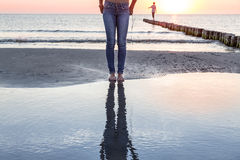 The legs of a woman reflected in the ocean Royalty Free Stock Photo