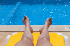 Legs of a woman relaxing poolside. Bare legs of a woman relaxing poolside lying sunbathing on a recliner chair with inviting cool blue water, conceptual Royalty Free Stock Image
