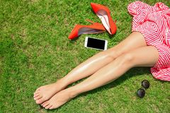Legs of woman resting on green grass. In sunny day Royalty Free Stock Photos