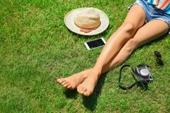 Legs of woman resting on green grass. In sunny day Stock Images