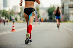 Legs woman runner in red compression socks. And blue kinesio tape on thigh royalty free stock photo