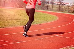 Legs of a woman running around the track Royalty Free Stock Photo