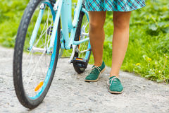 Legs of a woman in shoes with a bicycle Stock Photos