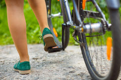 Legs of a woman in shoes with a bicycle Royalty Free Stock Images