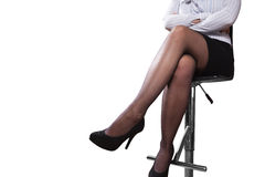Legs of a woman sitting on a bar stool Stock Photos
