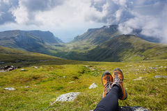 Legs of a woman sitting on the grass in the mountains Stock Photo