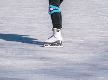 Legs of a woman with skates on ice. Ice skating recreational activity