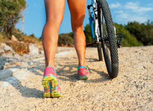 Legs of a woman in sneakers with a bicycle Stock Photos