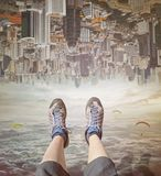 Legs of a woman in sneakers relaxing in sky. Invert city upside down .Future modern business industry concept: Big city on amazing sky at Bangkok, Thailand royalty free stock photo