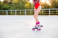 Legs of woman in swimsuit skating on roller skates outdoors Stock Image
