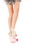 Legs of woman trying broke piggy bank Royalty Free Stock Image