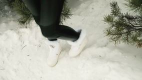 Legs of a woman trying to keep warm under spruce in frosty weather. Model dressed in a black tight pants and white short boots with fur trimming and stock video footage