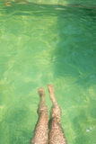 Legs of a woman underwater. In the swimming pool with green water Royalty Free Stock Photography