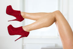 Legs of a woman wearing fishnet stockings and red ankle boots. Long and sexy female legs with red ankle boots Royalty Free Stock Photo