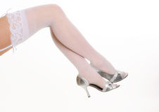 Legs of woman wearing white stockings and heels royalty free stock image