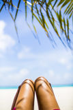 Legs of woman on white sandy beach, Maldives Stock Photography