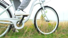 Legs of woman in white shoes riding retro bicycle countryside alone.  stock footage