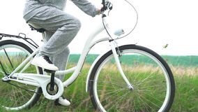 Legs of woman in white shoes riding retro bicycle countryside alone stock video