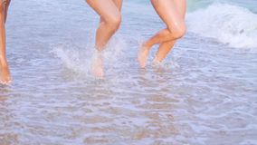 Legs womens tanned runing on sandy beach on sunset. Slim pretty girls go by the sea on golden sand. Friends on vacation. stock video footage