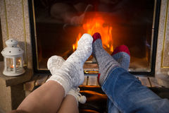 Legs in woolen socks stretched out heat up near fireplace. Legs of couple in woolen socks heat up near cozy fireplace, joined to each other in heart shape stock photo